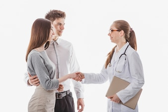 Woman doctor shaking hands with couple