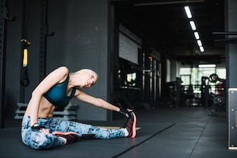 Woman doing stretching in gym