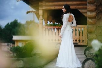 木製のポーチ背景にウェディングドレスに身を包んだ女