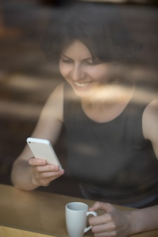 Woman drinking coffee and smiling while looking mobile