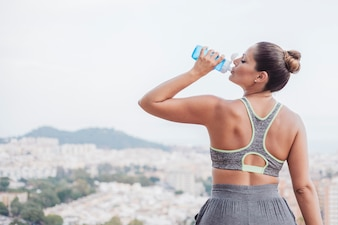Woman drinking water in front of city