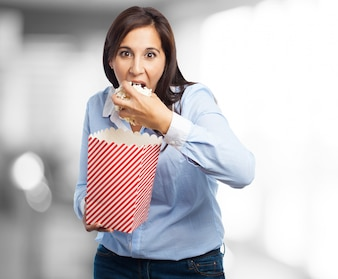 Woman eating popcorn with craving