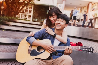 Woman embracing a man while he plays guitar