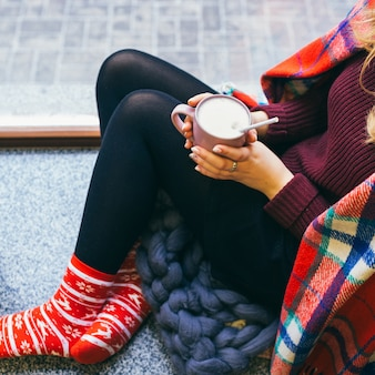 Woman enveloped in plaid sits on the floor with cup of hot chocolate