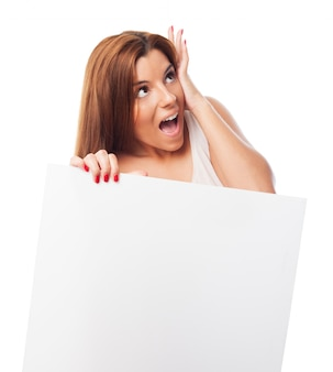 Woman fearfully looking up holding a panel