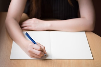 Woman hand writing on blank book