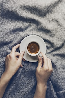 女は、グレーの格子縞の上に小さなカップでおいしいコーヒーエスプレッソを持っています。ホームコンセプト。上面図。
