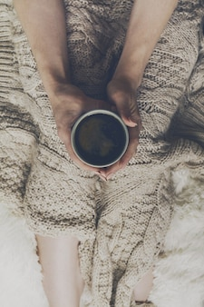 Woman hands holding tasty warm coffee espresso in ceramic cup sitting on bed with plaid. Home concept. Top View.