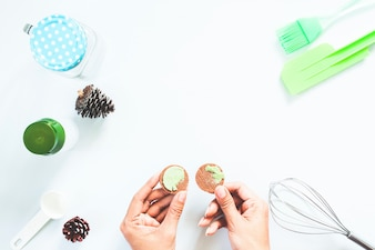 Woman hands with macha green tea cream cookie and bakery tools on white table, Flat lay