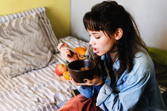 Woman having cereal on bed