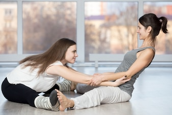 Woman helping another stretch back