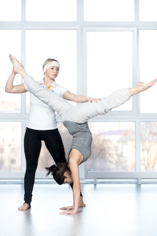 Woman helping another woman to stretch her legs