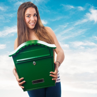 Woman holding a big green mailbox