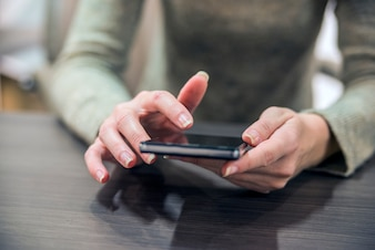 Woman holding a smartphone on the wooden table. Close-up hands of the girl, sitting at the wooden table, in one hand is smartphone. Businesswoman surfing the Internet on smartphone.