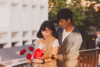 Woman holding roses while her boyfriend gives her a gift box