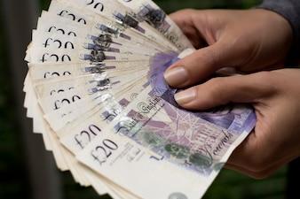 Woman holding twenty british pound banknotes