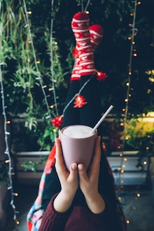 Woman holds in her hands cup with hot chocolate before her legs raised up