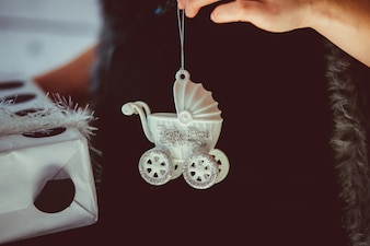 Woman holds white toy carriage on her pregnant belly