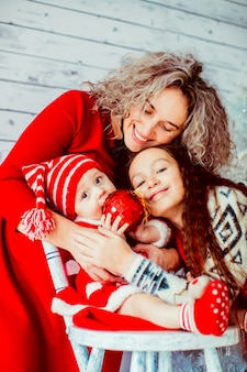 Woman hugging daughters wearing festive clothing