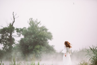 Woman in a white dress in a forest with fog