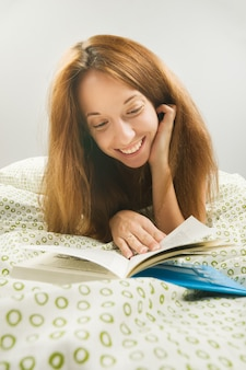 Woman in bed with book