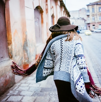 Woman in brown hat and cardigan walking