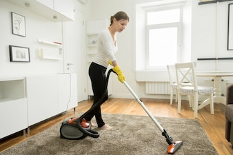 Woman in casual wear vacuum cleaning the carpet