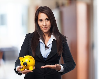 Woman in costume pointing a piggy bank