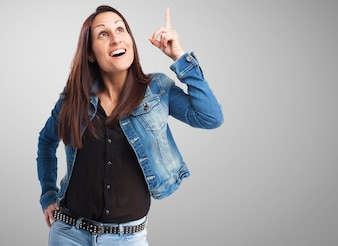 Woman in denim jacket pointing upwards