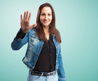 Woman in denim jacket with one hand raised and open