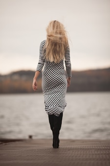 桟橋を歩くドレスの女