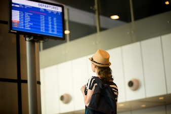 Woman in front of airport flight information panel