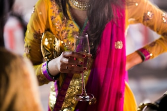 Woman in Hindu clothes holds glass of champagne