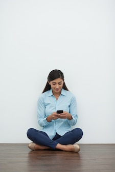 Woman in Lotus Position Using Smartphone