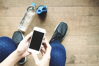 Woman in sport pants and shoes using smartphone, Top view