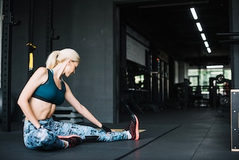 Woman in sports bra and leggings stretching