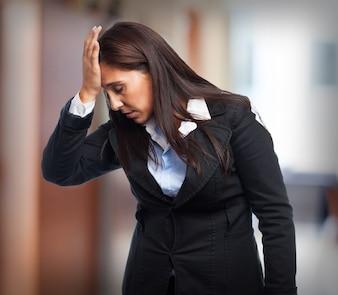 Женщина в костюме с головной болью