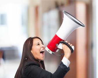 Woman in suit yelling through a megaphone