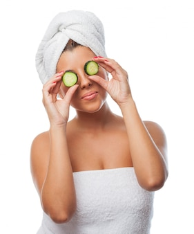 Woman in towel making cucumber eye mask