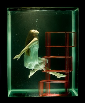 Woman in water with red bookcase looking up