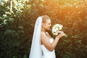 Woman in wedding dress smiling and smelling a bouquet