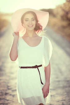 Woman in white dress walking at sunset