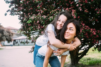 Woman leaning forward carrying girl