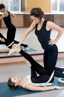 Woman leaning on another woman to stretch