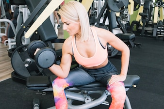 Woman lifting weight on exercise machine