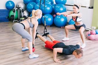 Woman lifting weights and man performing push-ups