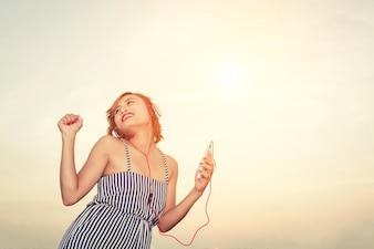 Woman listening to music and dancing outdoors