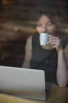 Woman looking at a laptop with a coffee