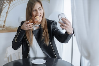 Woman looking at her mobile while eating a croissant