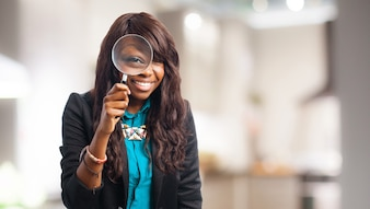 Woman looking through a magnifying glass